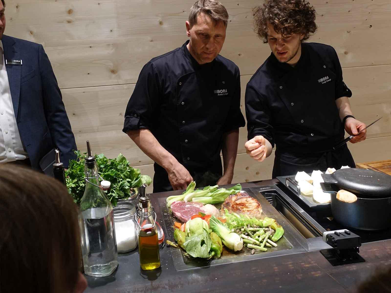 Die Köche von BORA zeigen die Funktion des Kochfeldabzugs beim Schaukochen