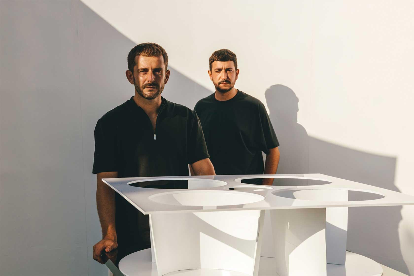 Portrait des Designerduos von MUT Design mit ihrem Modell vom Haus der Zukunft