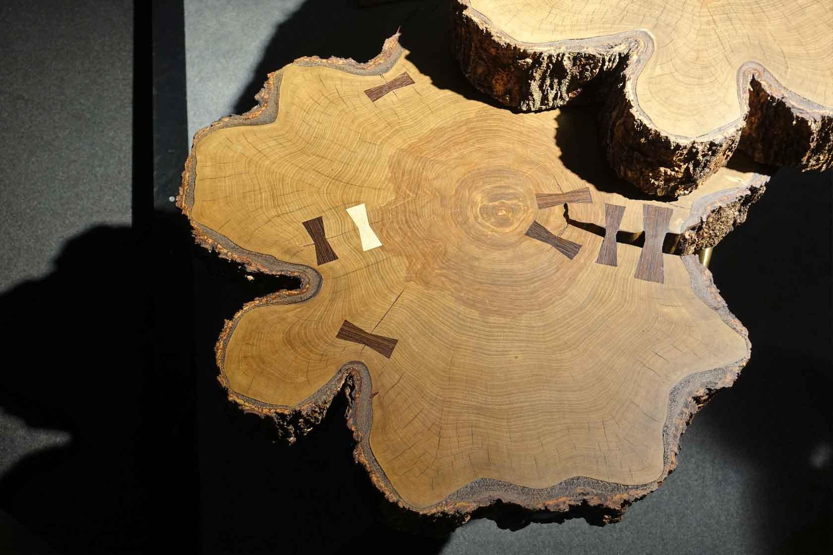Baumscheibe als Tischplatte mit feinen Intarsien in Schleifenform