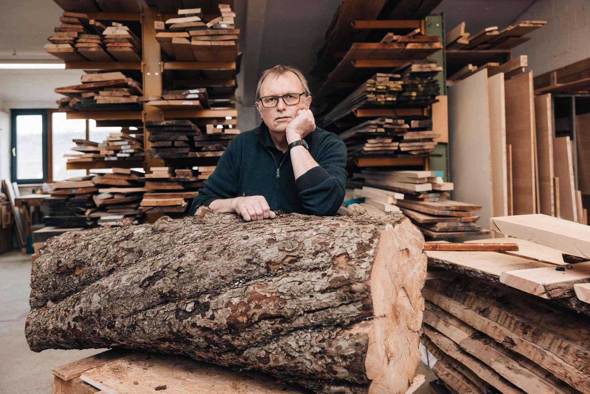 Geschäftsführer der Lignum Möbelmanufaktur Joachim Güntner mit einem Apfelbaumstamm in der Werkstatt.